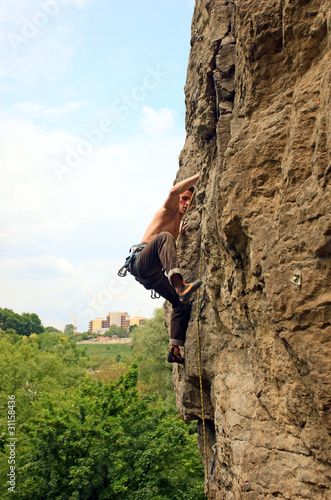 Rock climber on the cliff with mountainous background