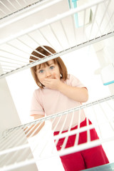 Child looking in empty fridge