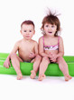 Two gay children in swimsuits sitting on a big air mattress.
