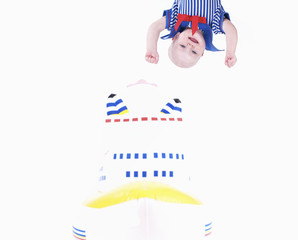 The little girl in a sailor dress hangs over a large toy ship.