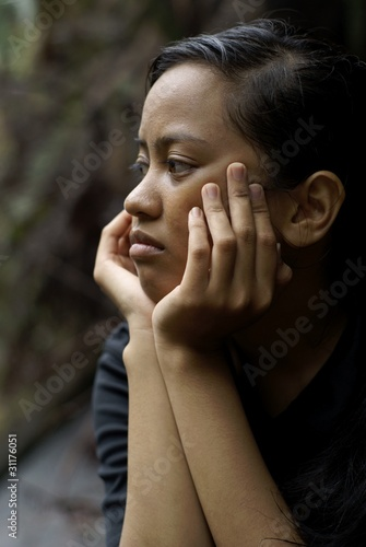 Troubled asian teen girl with hands holding face