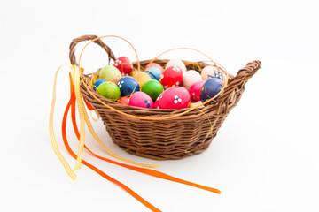 Geflochtener Korb gefüllt mit vielen bunten Eiern für Ostern