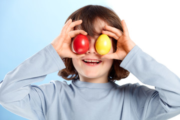 Little boy playing with colored easter eggs
