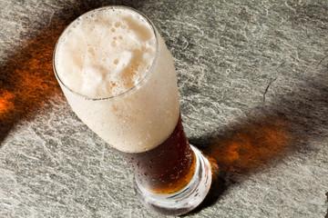 Cerveza negra con espuma y reflejo
