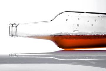 Botella de cerveza acostada con espuma