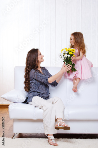 Girl presenting mother flowers