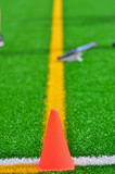 Cone & lacrosse stick on a turf field poster