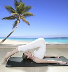 black mat yoga woman window view palm tree beach