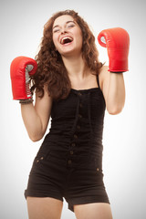 Young beautiful woman in boxing gloves celebrating victory