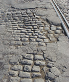 very old road with damaged asphalt , cobble-stone and tram-rails poster