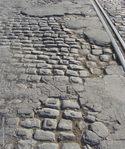 poster of very old road with damaged asphalt , cobble-stone and tram-rails