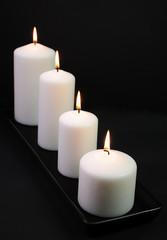 White decoration candles on black background
