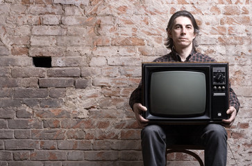 A man holding a retro television
