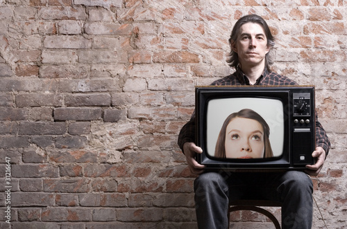 A man holding a retro TV with the head