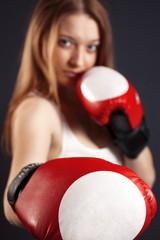 Красивая молодая девушка в боксерских перчатках.