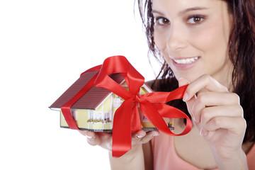 Hübsche junge Frau hält Haus mit Schleife in der Hand, quer