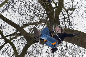junge Frau klettert auf einen Baum