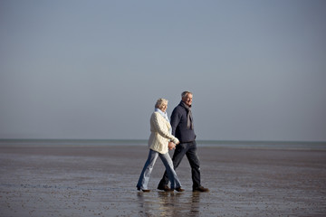 A senior couple walking on the beach, holding hands