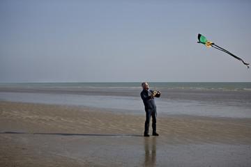 A senior man flying a kite on the beach