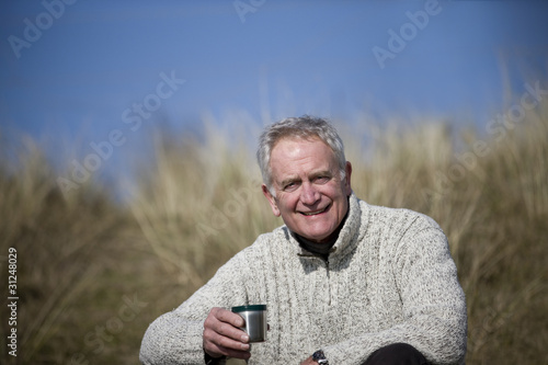 A senior man sitting amongst the sand dunes, having a hot drink