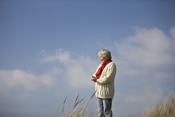 A senior woman standing outdoors