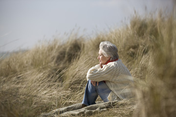A senior woman sitting amongst the sand dunes, thinking