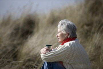 A senior woman sitting, holding a hot drink