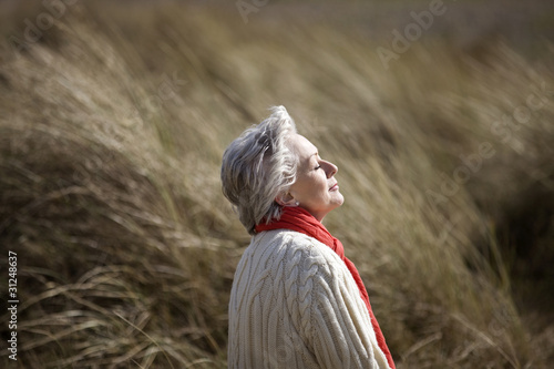 A senior woman sitting, enjoying the sun