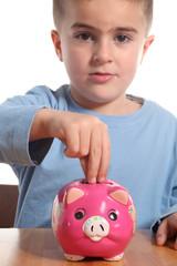 bambino inserisce moneta nel salvadanaio