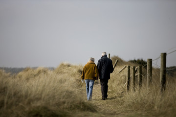 A senior couple walking along a path together, rear view