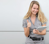 Beautiful blond woman using touchpad on grey background