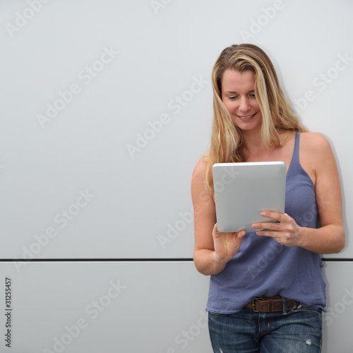 Smiling blond woman using electronic tablet on grey background