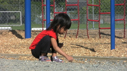 Little Girl Playing With Stones At Playground