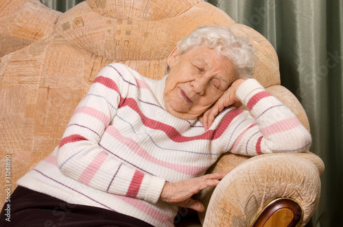 The elderly woman sleeps on a sofa