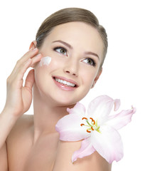 Happy teen with flower applying cream
