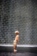 A Boy Standing Beside A Wall Fountain, Chicago, Illinois, Usa