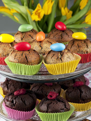 muffins decorated with easter eggs and tulips in the background