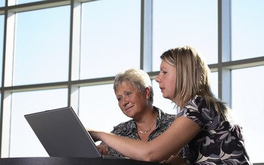 Two Women Looking At Personal Computer