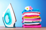Fototapety Pile of colorful clothes and electric iron  on blue background