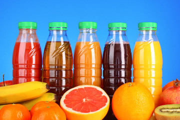 bottles of juice  with ripe fruits on blue background