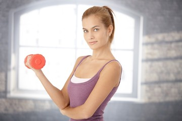 Smiling sporty woman with dumbbell