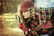 young woman with magnifier glass and hat