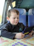 Enfant jouant à un jeu video dans le train poster