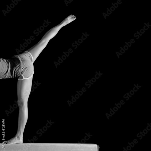 spread legs of female gymnast on balance beam