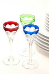 Colourful wine glasses and white plates
