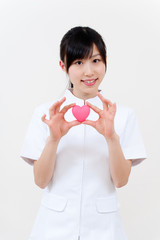 beautiful asian nurse holidng a symbol of heart