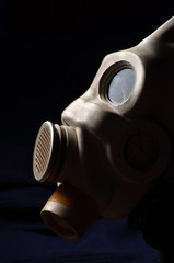 Closeup of a gasmask with blue dark background