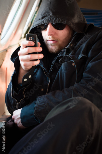 Hooded man looking at his cellular phone in an old airplane