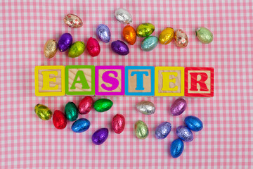 """Easter"" word in wooden block letters with chocolate eggs"