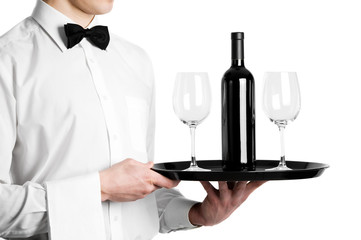 Waiter hands with wine bottle and stemware on tray
